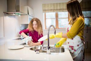 mama ayudando a su hija a lavar los trastes en la cocina en la casa
