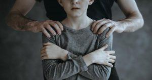 niño llorando y un hombre tocando sus hombros