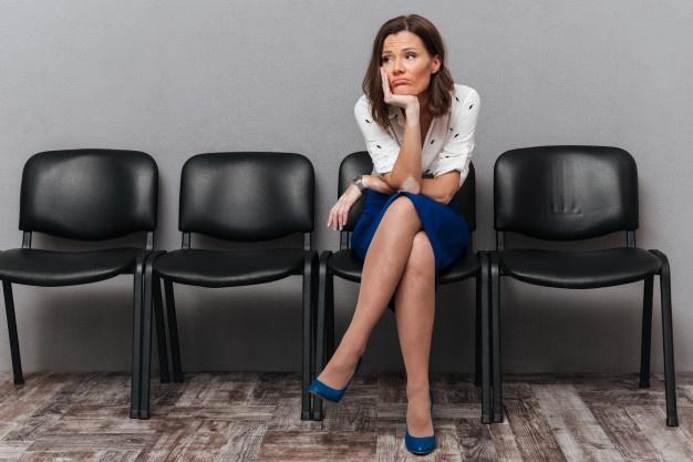 mujer sentada esperando disgustada