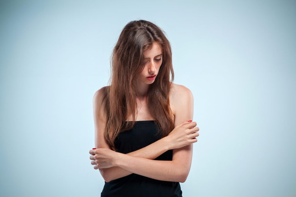 mujer triste con los brazos al rededor de ella