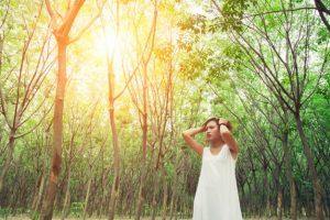 mujer en bosque con las manos en la cabeza